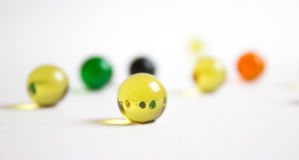 Refraction in Yellow Marble. A yellow marble refracting an image of marbles behind it Stock Images