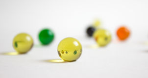 Refraction in Yellow Marble. A yellow marble refracting an image of marbles behind it Royalty Free Stock Photo