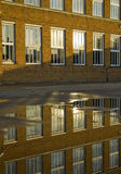 Refrection of a school building. In a large puddle Stock Photography