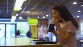 Refresco de apreciação fêmea novo que senta-se na tabela do café e que sorri na câmera vídeos de arquivo