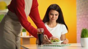 Refresco y hamburguesa de la porción del camarero al cliente femenino, bocado malsano almacen de metraje de vídeo