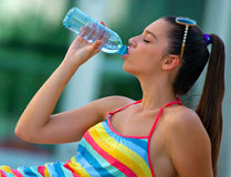Refreshing. Woman with water bottle refreshing herself Royalty Free Stock Images