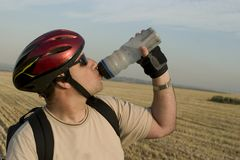 Refreshing. A bike rider refreshing himself after a long ride Royalty Free Stock Image
