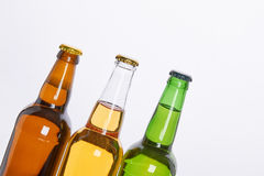 Refreshing alcoholic beverage, white background. Three bottles of beers with caps close up Stock Image