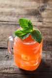 Refreshing alcoholic cocktails garnished with fresh mint. Refreshing fruity beverage garnished with fresh mint on rustic background royalty free stock photos