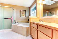 Refreshing bathroom with light wood cabinets, glass shower and b Royalty Free Stock Photo