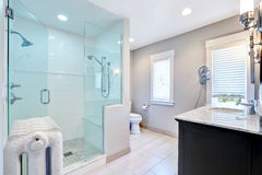 Refreshing bathroom with walk in shower and cast-iron radiator stock photos
