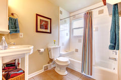 Refreshing bathroom with white tub and beige tile floor. Bright white and ivory bathroom with beige tile floor. White tub decorated with striped curtains stock photos