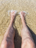 Refreshing at the beach. Legs and feet in the sand in shallow water spashed with a wave Stock Image