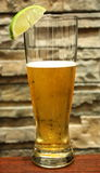 Refreshing beer with lime, brick background Royalty Free Stock Photo