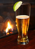 Refreshing beer with lime, fireplace background Royalty Free Stock Images