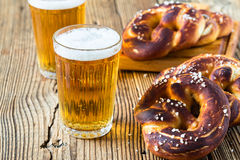 Refreshing beer ready to drink and fresh bavarian pretzels. Traditional food and drink for german octoberfest Stock Photography