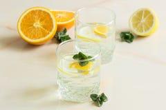 Refreshing birch juice with mint sliced lemon and orange. A refreshing fruit juice with sliced lemon and orange, mint on a light background Royalty Free Stock Photos