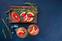 Refreshing bittersweet grapefruit lemonade with rosemary and cru. Shed ice on dark background, view from above Royalty Free Stock Image