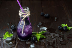 Refreshing blackberry juice in vintage eco style bottle on rustic dark wooden table. Cold summer berry drink with ice and mint Royalty Free Stock Photo