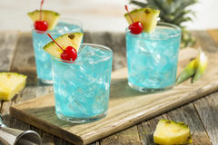 Refreshing Blue Hawaii Cocktail Punch. With Pineapple and Cherry royalty free stock photo