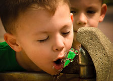 Refreshing ,boy drinking  from fountain. Two boys in summer drinking from a water foutain Stock Photos