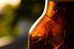 Refreshing Brown Cold Beer Bottle Covered With Condensation. A close-up shot of refreshing a brown cold beer bottle covered with condensation Royalty Free Stock Photography
