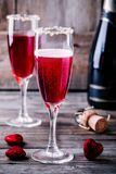 Refreshing cocktail with champagne and cranberry for Valentine`s day. On wooden background Royalty Free Stock Photos