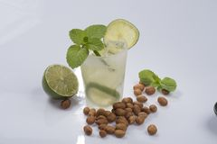 Refreshing cocktail with green lemon and ice. royalty free stock photos
