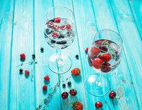 Refreshing cocktail with vodka martini with ice and berries on wood table.  Royalty Free Stock Photo