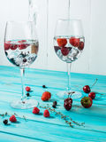 Refreshing cocktail with vodka martini with ice and berries on wood table.  Stock Images