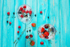 Refreshing cocktail with vodka martini with ice and berries on wood table. Top view Royalty Free Stock Photos