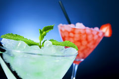 Refreshing cocktails of different colors over a blue lighted bac. Closeup of some cocktail glasses with beverages of different colors garnished with mint leaves royalty free stock image