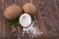Refreshing coconuts on a wooden background. Tasteful cracked coco full of white flakes. Delicious coconuts with a green leaf. A close-up of three round coconuts Stock Images