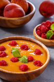 Refreshing cold peach soup garnished with raspberries and mint l Stock Photo