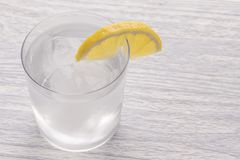 Refreshing cold water with lemon. With ice. Ready to eat. Next is a knife after cutting fruit. Misted glass. Refreshing cold water with lemon in a wet glass with royalty free stock image