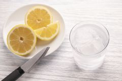 Refreshing cold water with lemon. With ice. Ready to eat. Next is a knife after cutting fruit. Misted glass stock photography