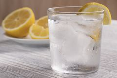 Refreshing cold water with lemon. With ice. Ready to eat. Next is a knife after cutting fruit. Misted glass stock photo