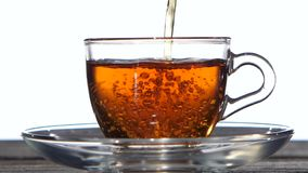 Refreshing cup of green tea. Closeup. Slow motion. Refreshing cup of green tea, saucer standing on a wooden table, set of dishes made of transparent glass stock video