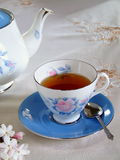 Refreshing Cup of Tea. A cup of tea with related items and Jasmine flowers on an embroidered tablecloth Stock Image
