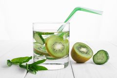 Refreshing drink for detoxification, mineral water in a glass, fresh green kiwi, mint and cucumber on a white table royalty free stock photography