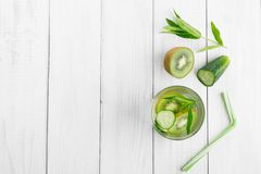 Refreshing drink for detoxification, mineral water in a glass, fresh green kiwi, mint and cucumber on a white table stock photo