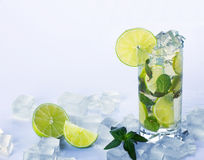 Refreshing  drink. With green lime, leafs of  mint and many cubes of ice on table with water drop on light blue background Royalty Free Stock Photo