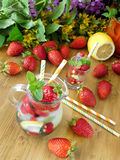 Refreshing drink with ice cubes, strawberries and mint in a glass jug Stock Photo