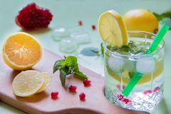 Refreshing drink with lemon and ice. Lemonade with mint ice and a tub on a wooden board, refreshing drink Royalty Free Stock Image