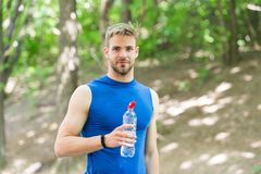 Refreshing drink. Man athletic sportsman hold bottle water. Athlete drink water after training in park. Vitamins and. Minerals. Man athlete sport clothes care stock photos