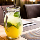 A refreshing drink in the pitcher on the table. Chilled juice with ice and mint Stock Photo
