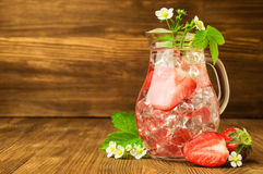 Refreshing drink with a strawberry and ice in a glass jug Stock Photography