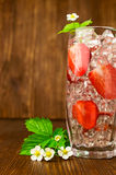 Refreshing drink with a strawberry and ice Stock Images