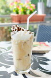 Refreshing frappe. Refreshing frappuccino with whipped cream and chocolate syrup and a straw Royalty Free Stock Image