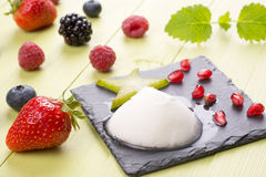 Refreshing frozen sorbet on table with fresh fruits. Frozen sorbet with mixed fresh fruits on table Royalty Free Stock Photos