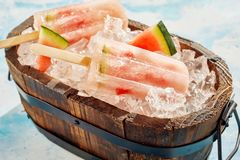 Refreshing frozen watermelon popsicles in a tub. Refreshing healthy frozen watermelon popsicles in a wooden tub chilling on crushed ice with slices of t ready stock images