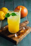 Refreshing fruit drink detox. Summer orange lemon cocktail with ice and mint close up. Dietary fruit drink with backlight on a woo royalty free stock image