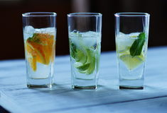 Refreshing fruit fresh. From the lemon orange and lime with ice and mint in a glass on a white wooden table Stock Images