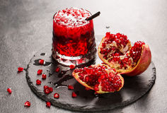 A refreshing fruity beverage and a cut garnet on a gray background. Red non-alcoholic drink with ice. Fresh bittersweet Stock Images